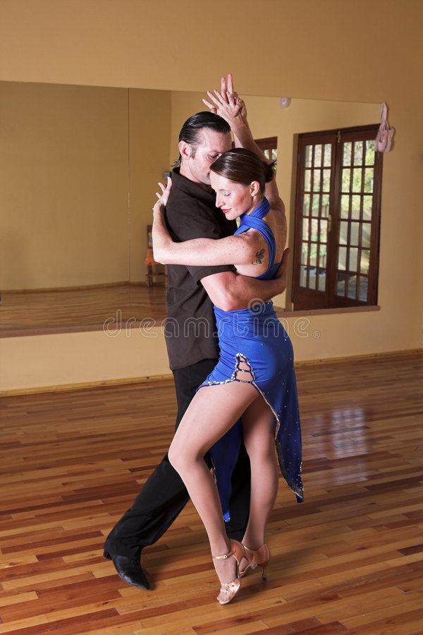 Two ballroom dancers practicing in their studio. A young adult couple dancing and practicing ballroom dancing together in a studio - Focus on woman stock photography