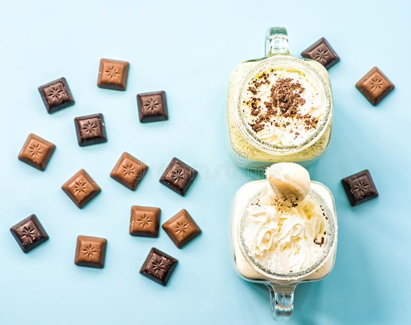 Two banana and kiwi milkshakes in mason jars with creme on top decorated with chocolate pieces scattered. flat lay top view smooth. Two banana and kiwi stock image