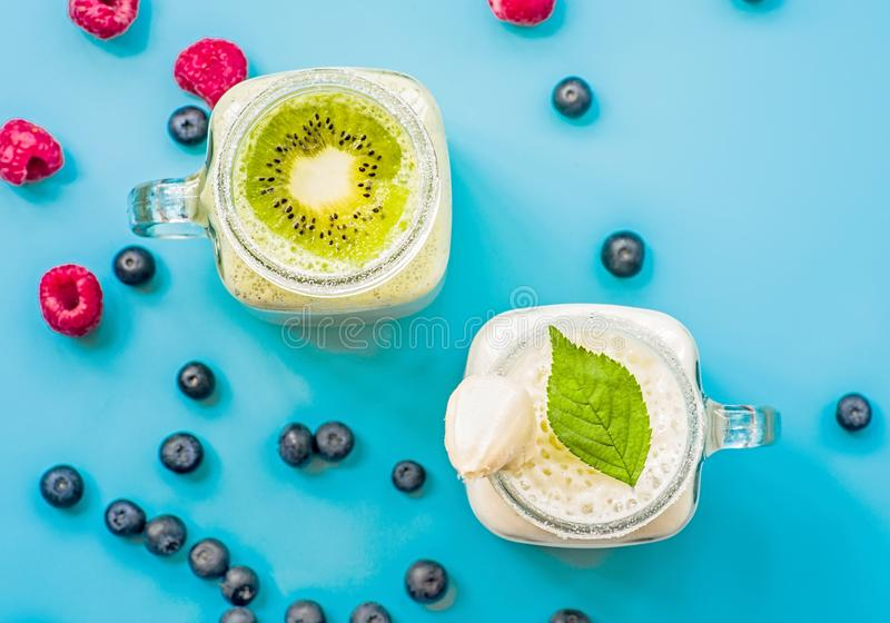 Two banana and kiwi milkshakes in mason jars with creme on top decorated with raspberries and blueberries. flat lay top view smoot. Hie on blue background royalty free stock images