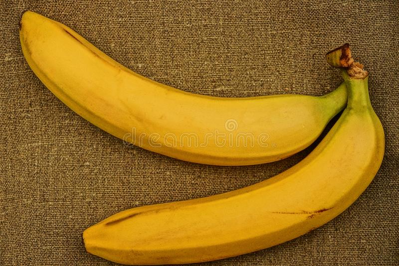 Two bananas on a gray sacking stock images
