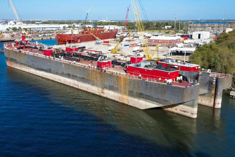 Two Barge Tankers. Two ocean going sulfur tanker barges docked for repairs and to ship out royalty free stock photo