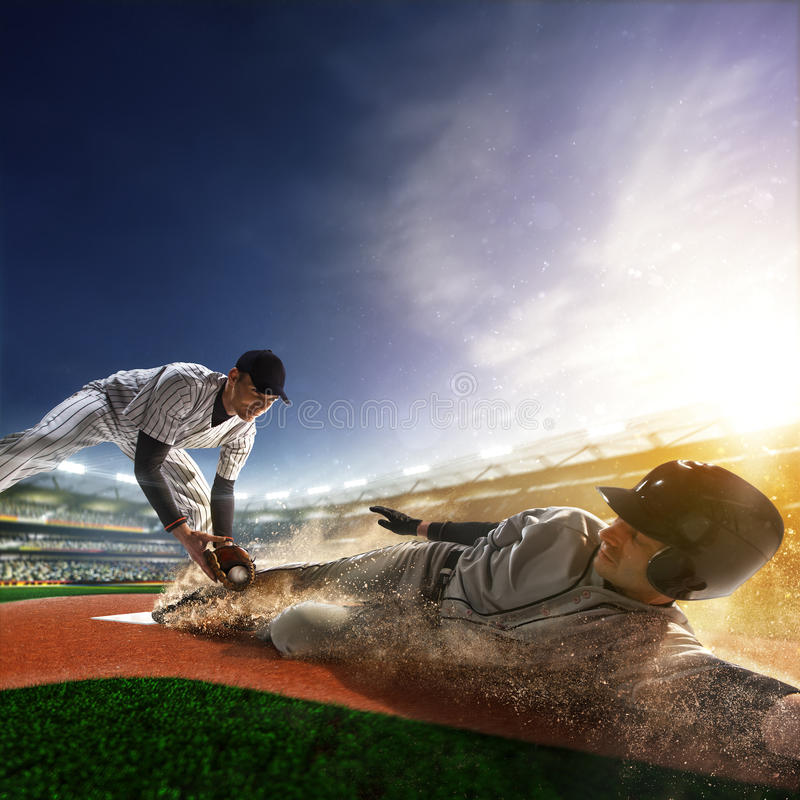 Two baseball player in action. Two baseball player the in action on grand arena royalty free stock image