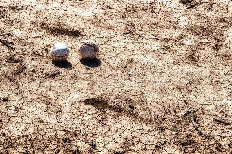 Two Baseballs On Sun Baked Ground. Two baseballs, one with a torn cover laying on sun baked and cracked ground royalty free stock image