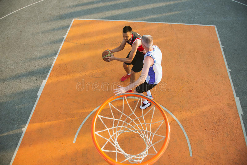 Two basketball players on the court outdoor.  stock photography