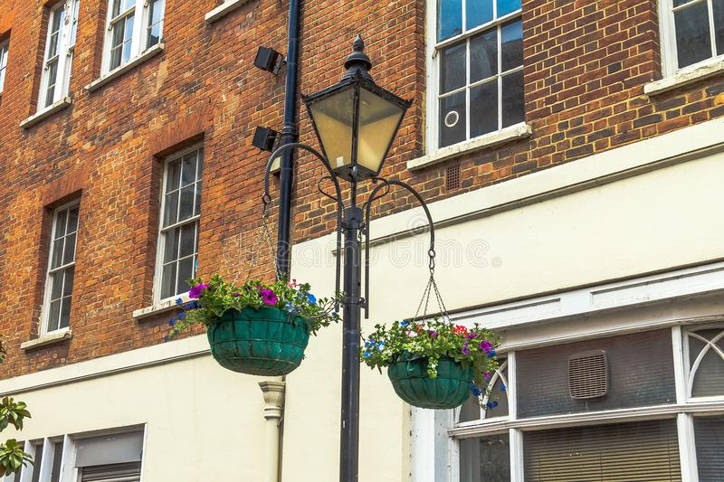 Two baskets of flowers on a lamp post in Windsor town. Two baskets of flowers on a lamp post in the Windsor town, UK royalty free stock photography