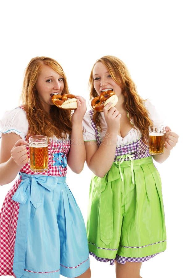 Two bavarian dressed women eating pretzels