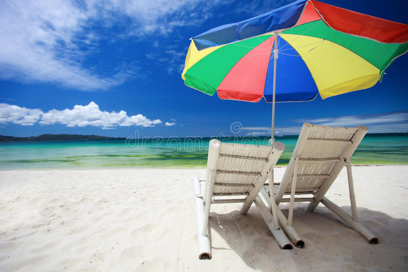 Two beach chairs and colorful umbrella stock photo