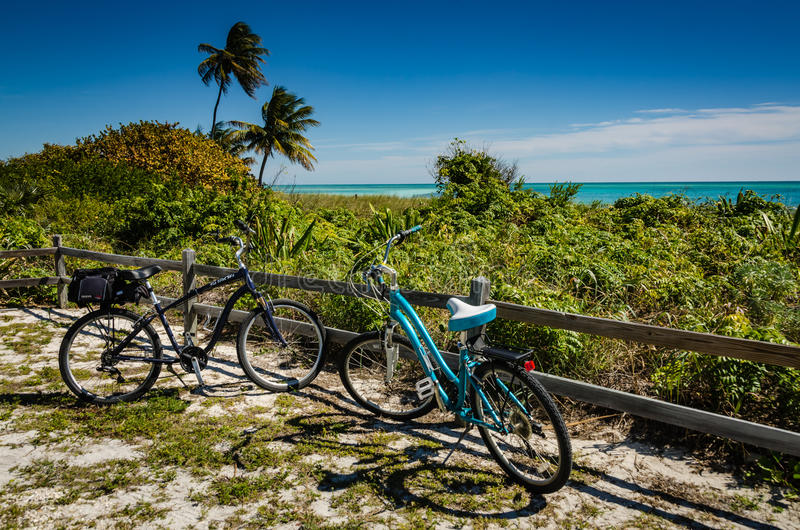 Two Beach Cruisers - Bahia Honda, Florida. Two bicyles, one with a saddle bag, sit parked by a wooden fence on the beach at Bahia Honda State Park in the Florida stock images