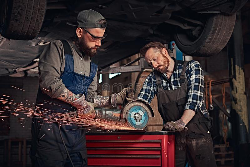 Two bearded auto mechanic in a uniform and safety glasses working with an angle grinder while standing under lifting car stock images