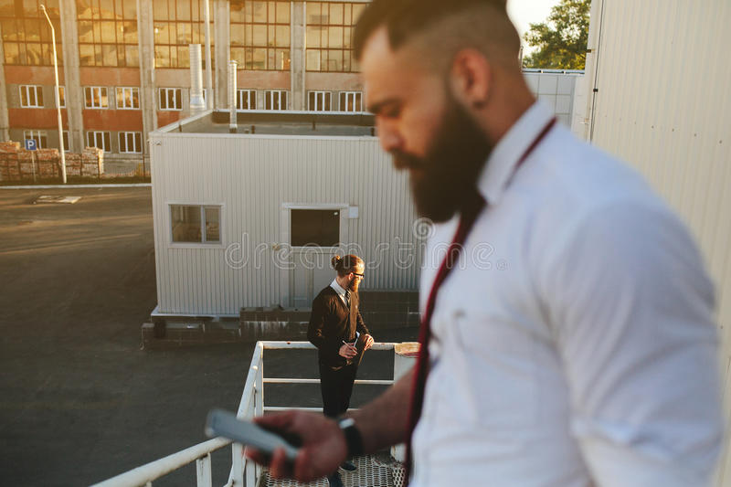 Two bearded businessman looking at something stock images