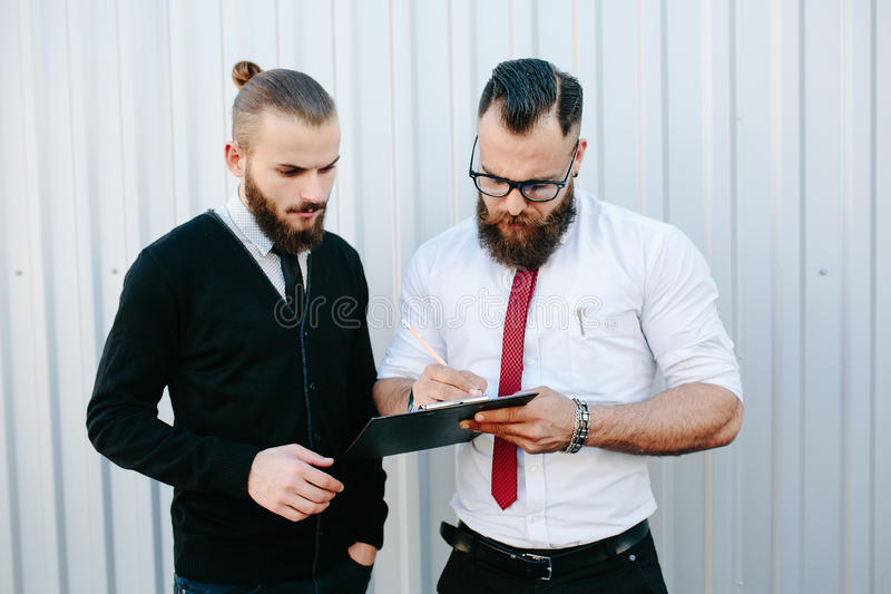 Two bearded businessman signing documents royalty free stock images