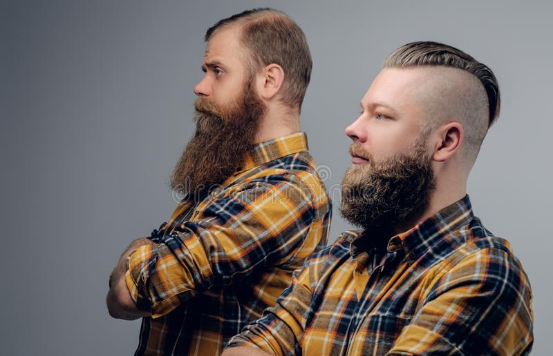 Two bearded hipsters dressed in a yellow plaid shirt. Two bearded hipsters dressed in a yellow plaid shirt isolated on grey vignette background royalty free stock photo