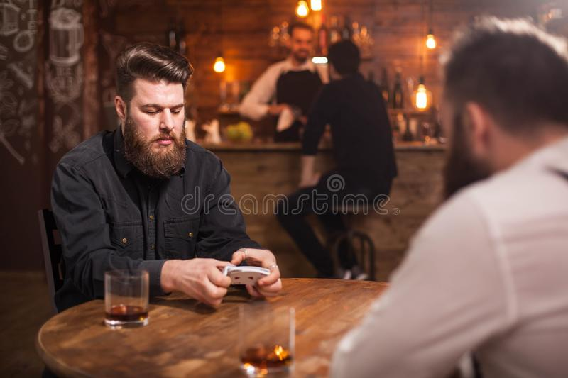 Two bearded hipsters playing a card game in a pub. Two bearded hipsters playing a card game in a vintage pub. A bartender with a client is in the background royalty free stock photography