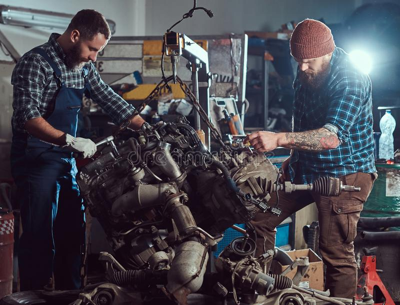 Two bearded mechanics specialist repairs the car engine which is raised on the hydraulic lift in the garage. royalty free stock photo