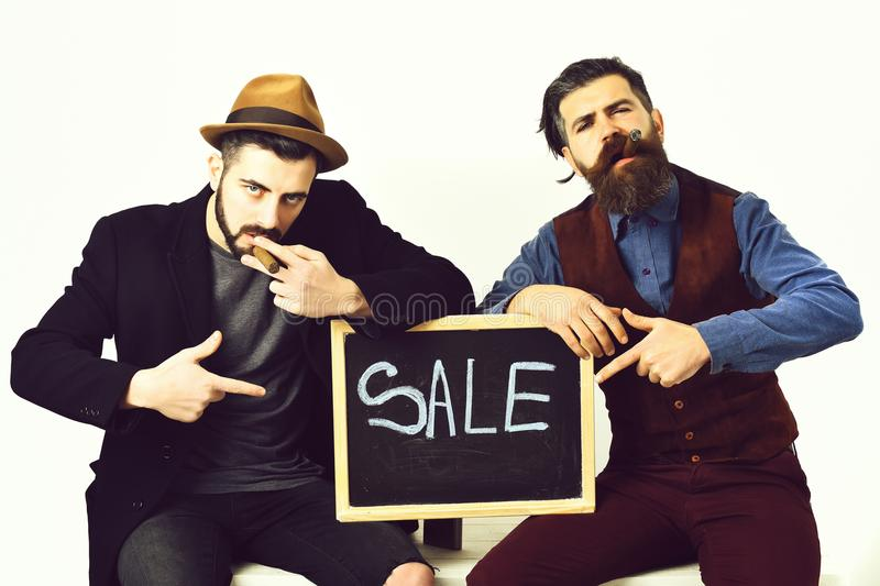 Two bearded mens, caucasian stylish hipsters with moustache, sale inscription. Two bearded mens, short and long beard. Caucasian stylish hipsters with moustache stock images