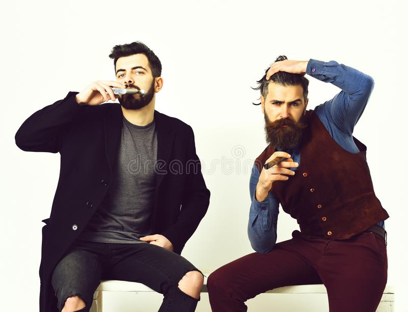 Two bearded mens, caucasian stylish hipsters with moustache. Two bearded mens, short and long beard. Caucasian stylish hipsters with moustache, holding flask royalty free stock photography