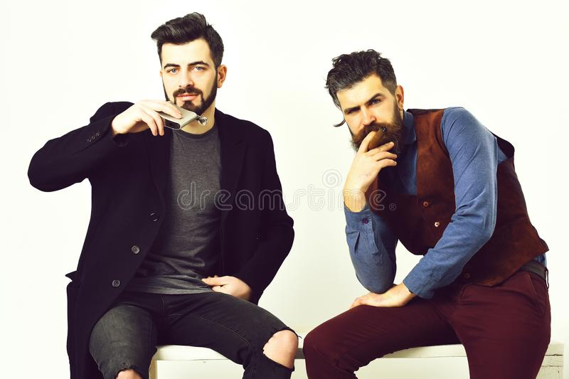 Two bearded mens, caucasian stylish hipsters with moustache. Two bearded mens, short and long beard. Caucasian stylish hipsters with moustache, holding flask royalty free stock images