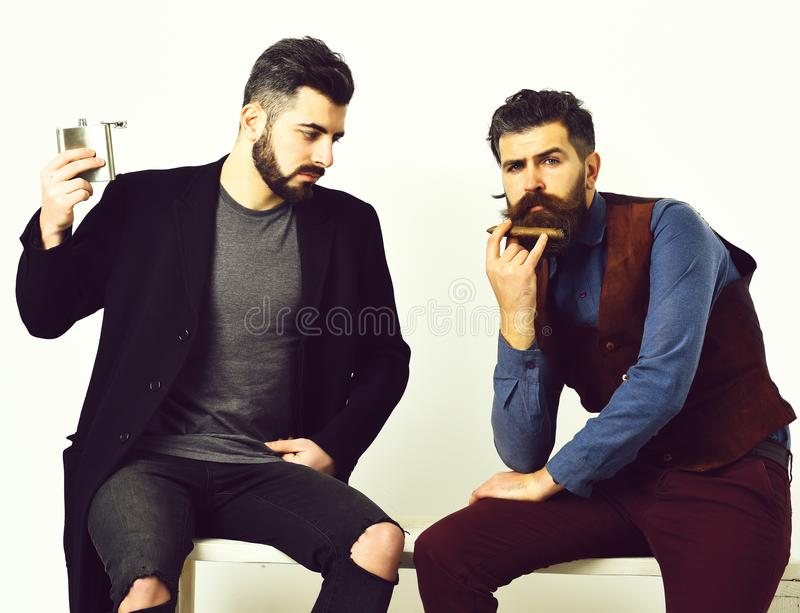 Two bearded mens, caucasian stylish hipsters with moustache. Two bearded mens, short and long beard. Caucasian stylish hipsters with moustache, holding flask stock image