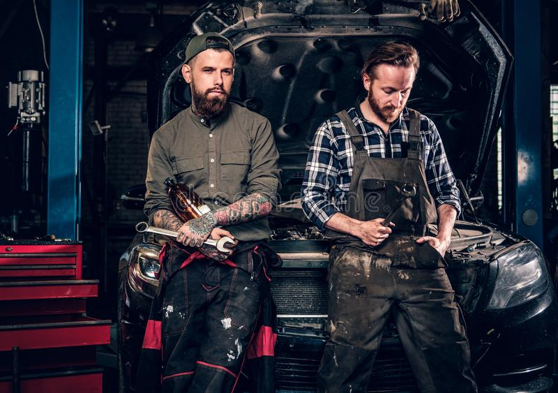 Two bearded tattooed mechanics near the car in a workshop. Two bearded tattooed mechanics with nut key near the car with open engine hood in a workshop stock images