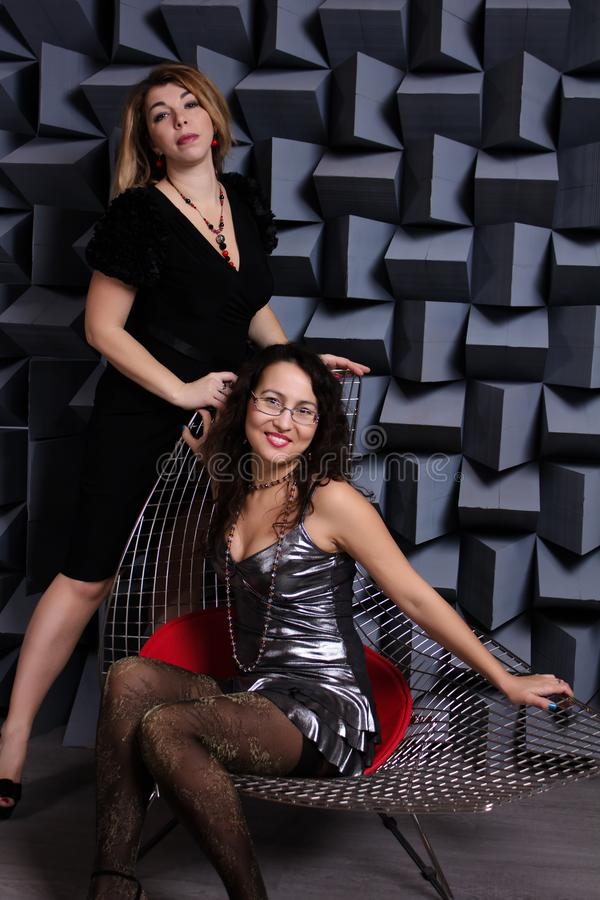 Two beautiful women asian and caucasian in black night fashion dress posing on a gray background. Studio shot stock images