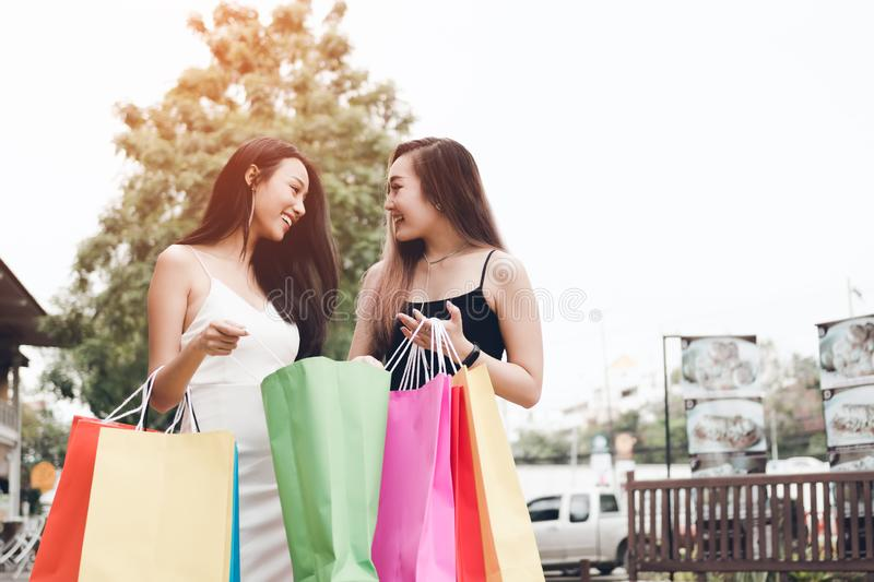 Two beautiful asian female friends standing checking in paper ba stock images