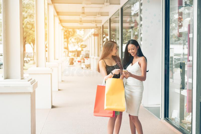 Two beautiful asian female friends standing and looking in paper royalty free stock image