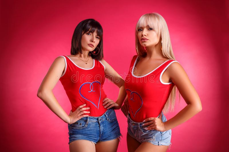 Two beautiful athletic young women posing in Studio on pink background royalty free stock images