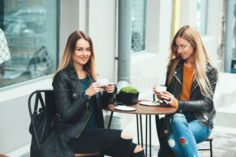 Two beautiful attractive stylish women are sitting outdoor in cafe drinking coffe and tea talking and enjoying great day. stock photos