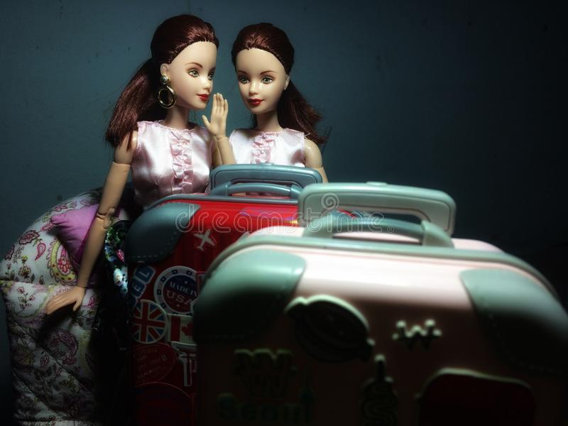 Two beautiful Barbie dolls are whispering some secret stock photos