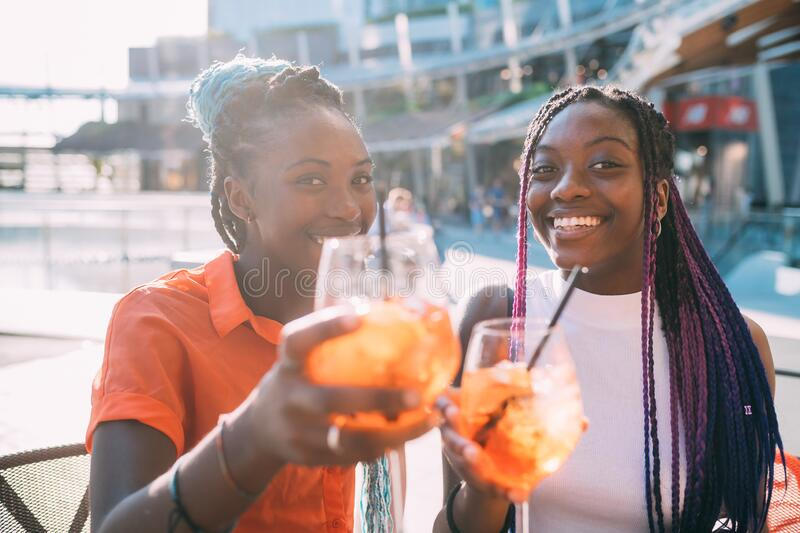 Two beautiful black women sisters sitting bar making a toast smiling. Celebrating, success, togetherness concept stock photo