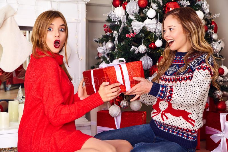 Two beautiful blond girls near decorated Christmas tree royalty free stock images
