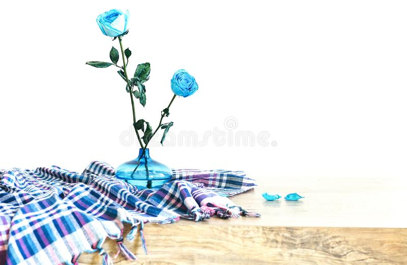 Two beautiful blue rose flowers with green leaves in a blue glass vase decorated with the checkered tablecloth and rose petals. royalty free stock photography