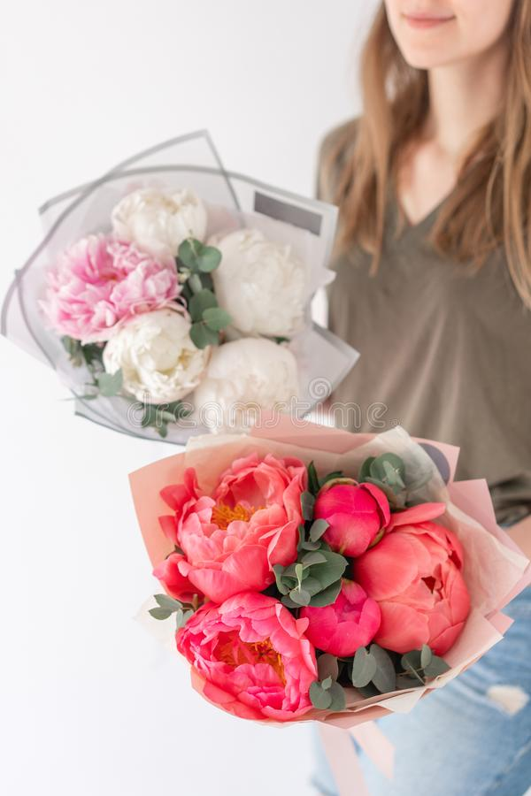 Two Beautiful bouquets. Coral and white peonies in womans hand. Beautiful peony flower for catalog or online store stock photography