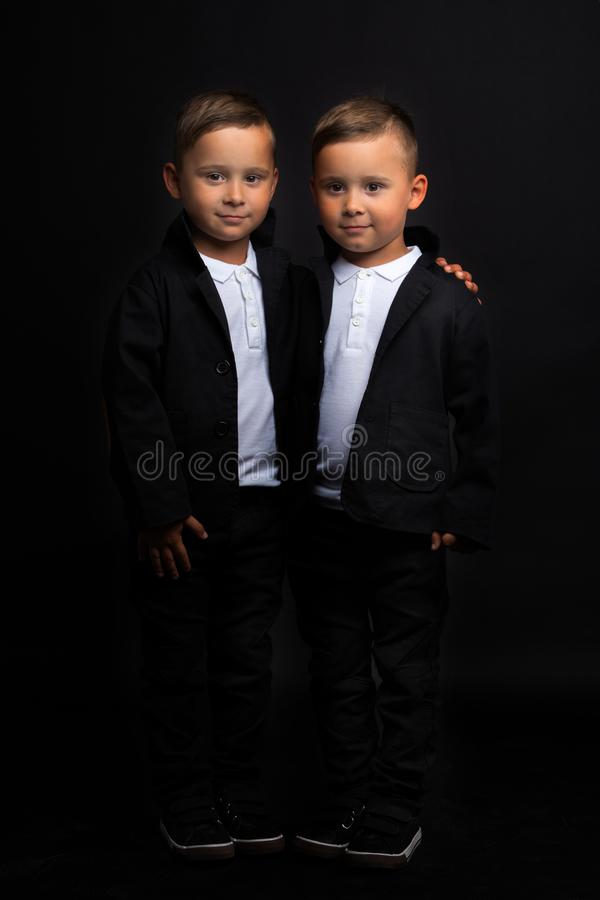 Two beautiful boys in black suits stock photo