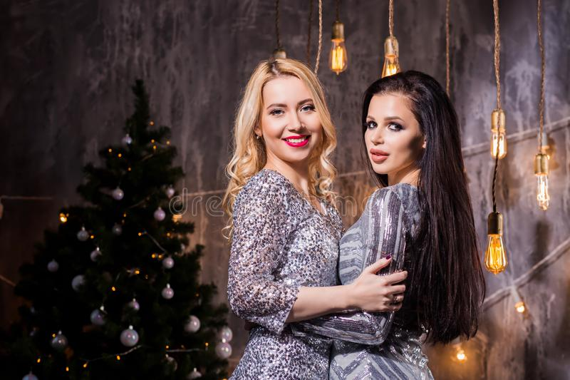Two beautiful brunette and blonde women in silver sparkly dresses for the Christmas tree and lights. Holidays, New Year, celebration and people concept royalty free stock images