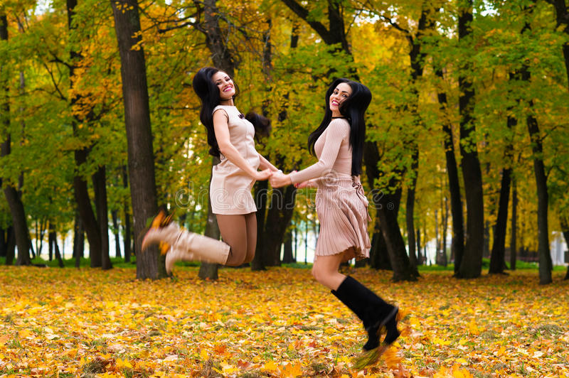 Two beautiful brunette girls jumping on background autumn park stock image