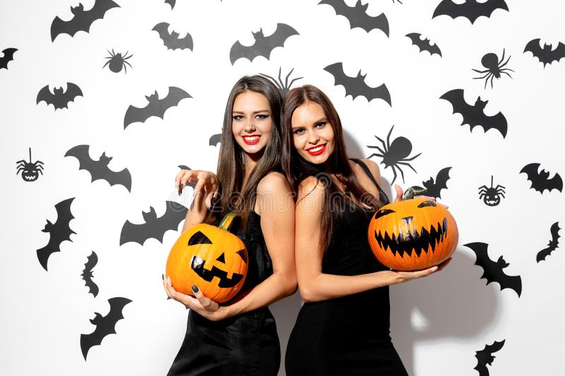 Two beautiful brunette women in black dresses have fun with jack-o-lanterns on a white background with bats and spiders royalty free stock photos