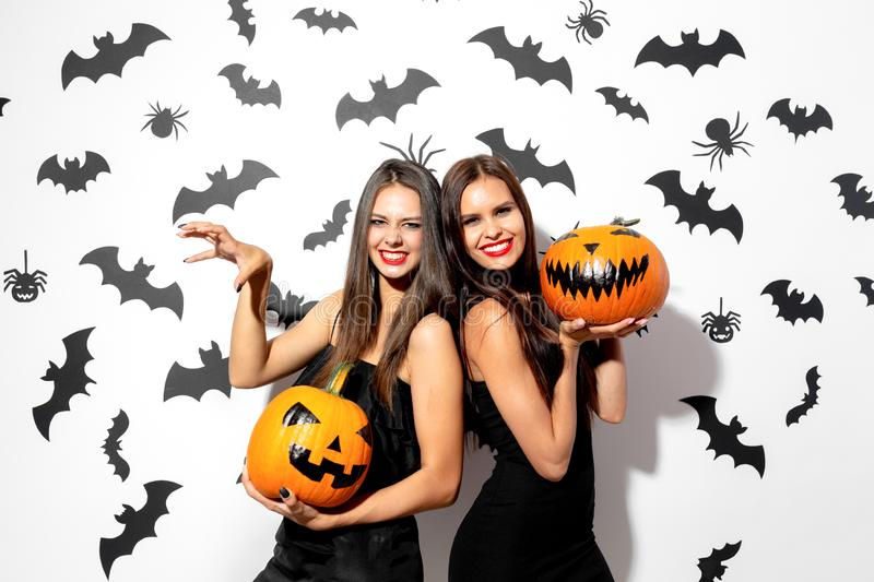 Two beautiful brunette women in black dresses have fun with jack-o-lanterns on a white background with bats and spiders royalty free stock images