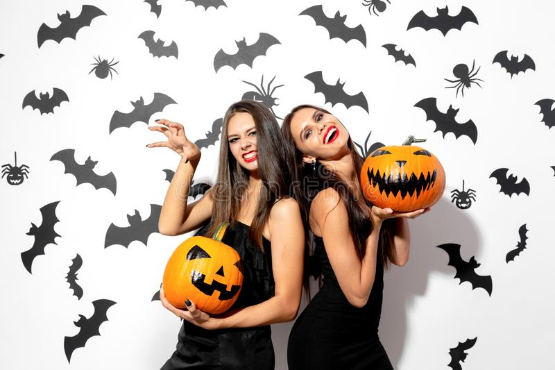Two beautiful brunette women in black dresses have fun with jack-o-lanterns on a white background with bats and spiders stock photo
