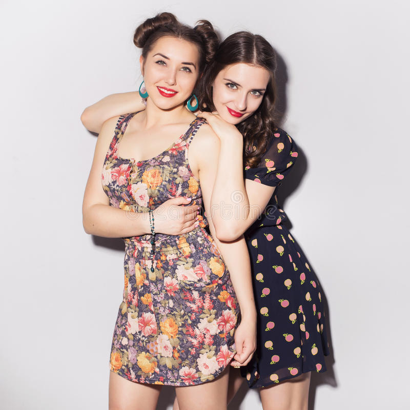 Two beautiful brunette women (girls) teenagers spend time together having fun, make funny faces. Casual hipsters outfit: romantic stock images