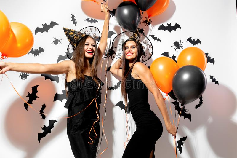 Two beautiful brunette women in witches hats are with black and orange balloons on a white background with bats and royalty free stock photo