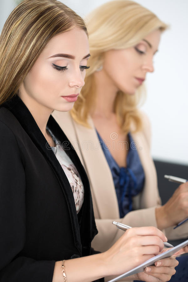 Two beautiful business women sitting at seminar and writing some royalty free stock image