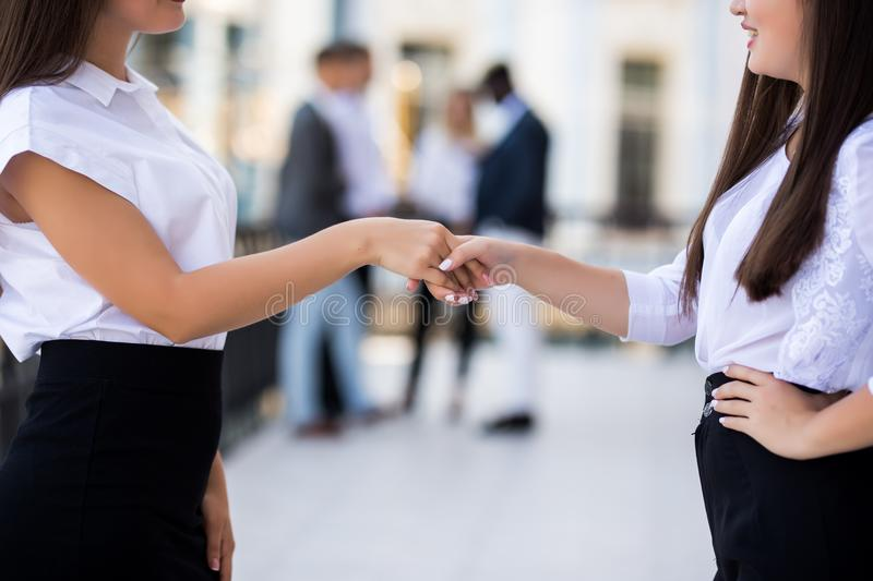 Two beautiful businesswomen handshaking in office in front of business team. Succesful agreement at meeting stock photography