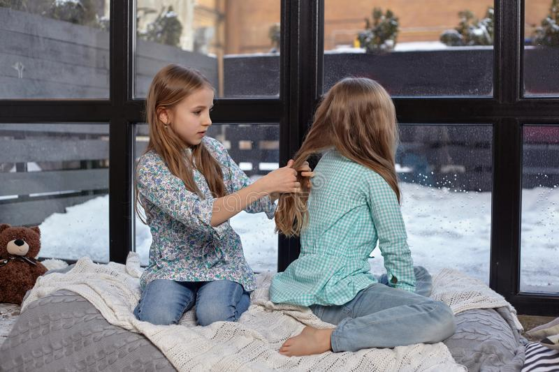 The image of two cute little sisters sitting on windowsill in peace and quiet. Two beautiful caucasian sisters sitting on the windowsill, they look out of the royalty free stock photo