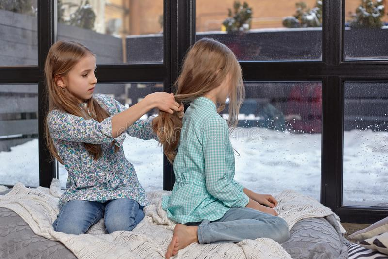 The image of two cute little sisters sitting on windowsill in peace and quiet. Two beautiful caucasian sisters sitting on the windowsill, they look out of the royalty free stock image