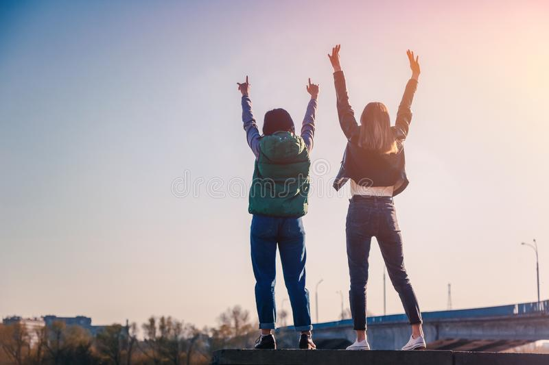 Two beautiful cool teenage girls 15-16 years old, best friends having fun, with their hands up royalty free stock images
