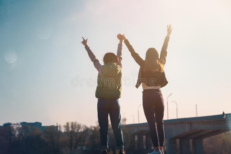 Two beautiful cool teenage girls 15-16 years old, best friends having fun, with their hands up stock photos