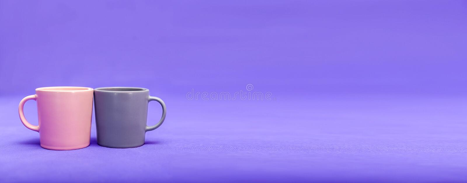 Two beautiful cups of pink and gray are on a purple background. The concept of the holiday - Valentine`s Day, Mother`s Day, royalty free stock photo