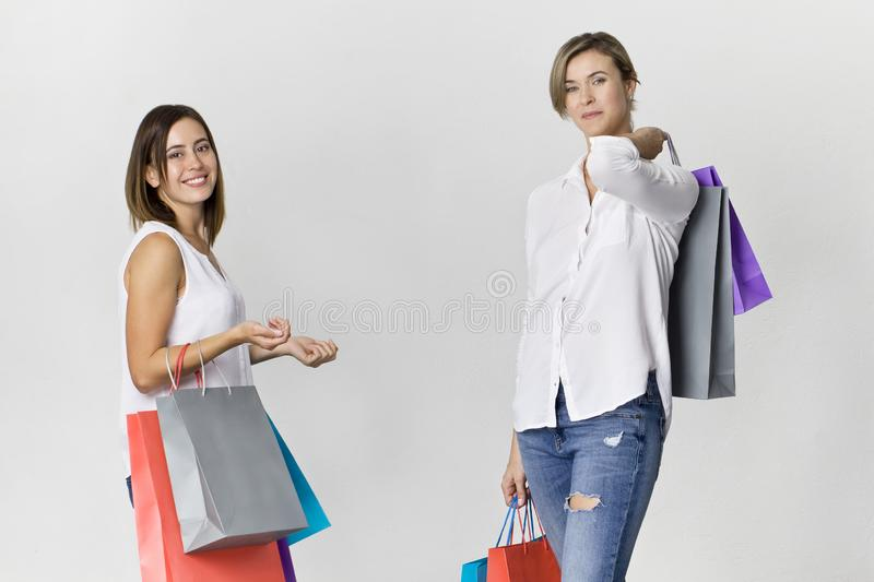 Two beautiful female friends on shopping with colorful bags. Too stock photography