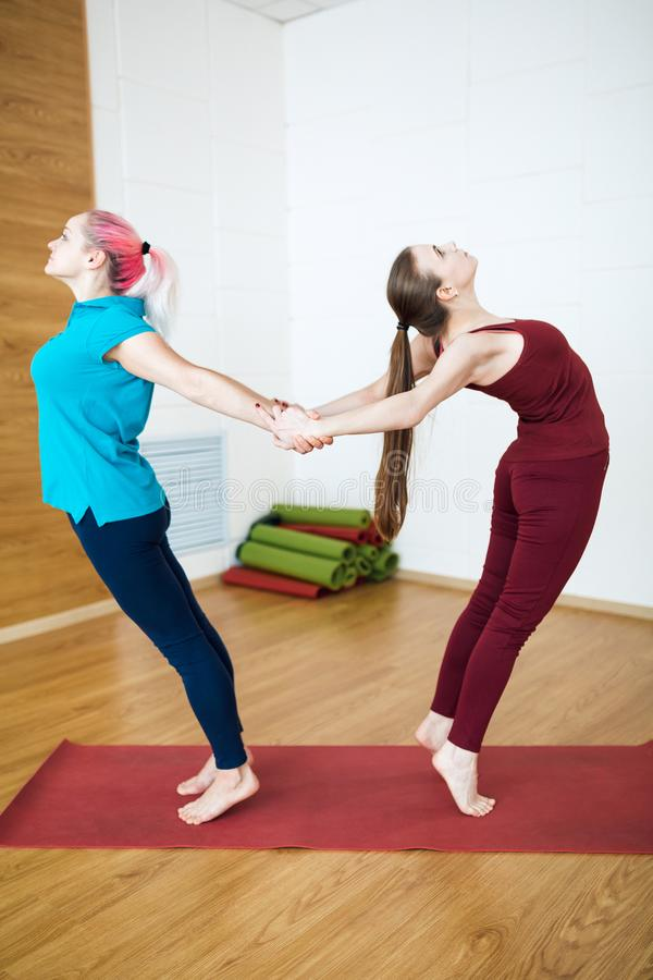Two beautiful fitness girls made stretching in the gym. stock photos